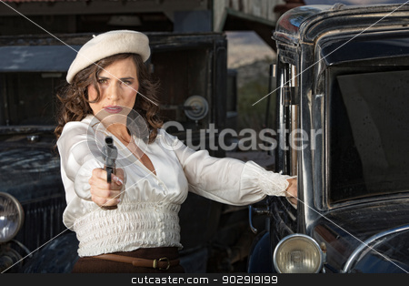 Tough Woman Holding Gun stock photo, Retro 1920s era female gangster aiming gun next to car by Scott Griessel