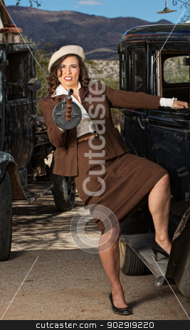 Pretty Woman Firing Machine Gun stock photo, Pretty woman next to vintage car holding machine gun  by Scott Griessel