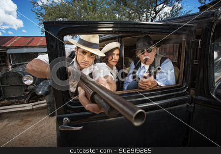 Three 1920s Era Gangsters stock photo, Three 1920s vintage gangsters outside aiming weapons through a window by Scott Griessel