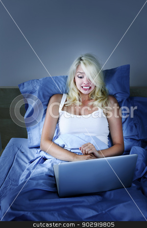 Frightened woman with computer at night stock photo, Scared woman using laptop computer in bed at night by Elena Elisseeva