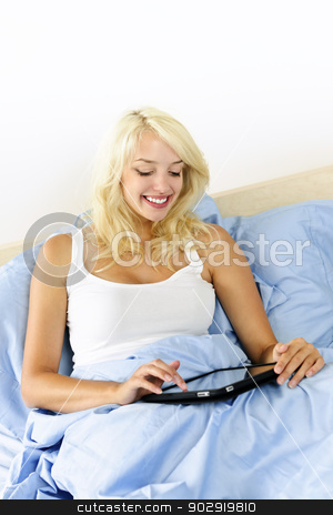 Woman sitting in bed with tablet device stock photo, Happy blonde woman using tablet computer sitting in bed by Elena Elisseeva