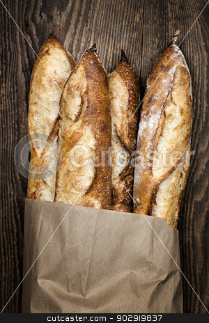 Baguettes bread stock photo, Four baguette bread loaves in paper bag on wooden background by Elena Elisseeva