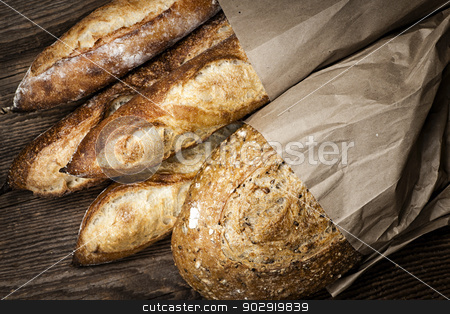 Artisan bread stock photo, Fresh baked rustic bread loaves in paper bags on dark wood background by Elena Elisseeva