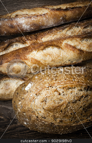 Artisan bread stock photo, Fresh baked rustic bread loaves on dark wood background by Elena Elisseeva