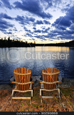 Wooden chairs at sunset on lake shore stock photo, Landscape with adirondack chairs on shore of relaxing lake at sunset in Algonquin Park, Canada by Elena Elisseeva