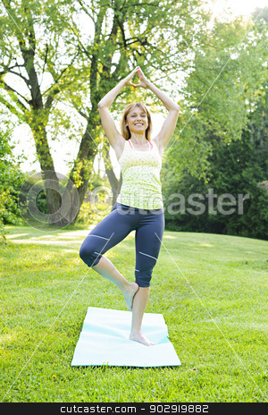 Woman in yoga tree pose stock photo, Female fitness instructor doing yoga tree or vrksasana pose in green park by Elena Elisseeva