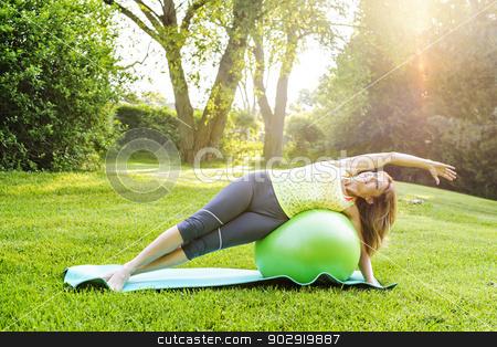 Woman on yoga balance ball stock photo, Female fitness instructor using yoga exercise ball  outdoors in morning sunshine by Elena Elisseeva