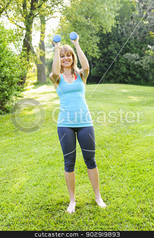 Woman exercising with dumbbells stock photo, Female fitness instructor exercising with small weights in green park by Elena Elisseeva