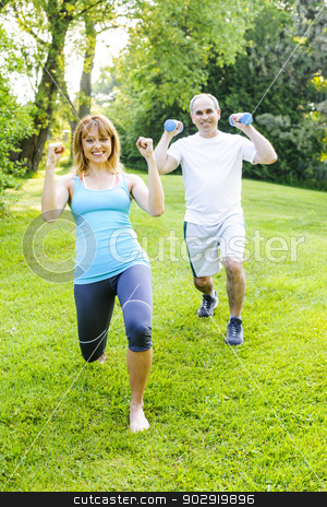 Personal trainer with client exercising stock photo, Female fitness instructor exercising with middle aged man in green park by Elena Elisseeva
