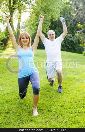 Personal trainer with client exercising outdoors stock photo, Female fitness instructor exercising with middle aged man in green park by Elena Elisseeva