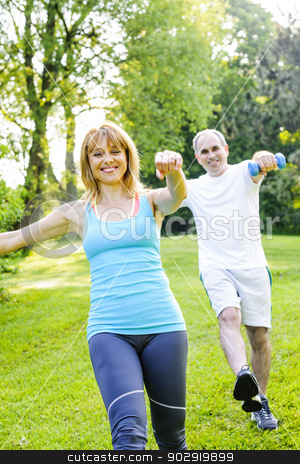 Personal trainer with client exercising in park stock photo, Female fitness instructor exercising with middle aged man outdoors in green park by Elena Elisseeva
