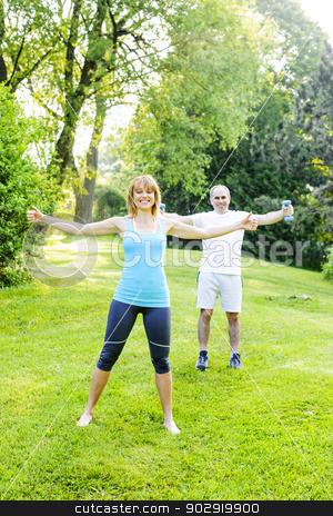 Personal trainer with client exercising outside stock photo, Female fitness instructor exercising with middle aged man outdoors in green park by Elena Elisseeva