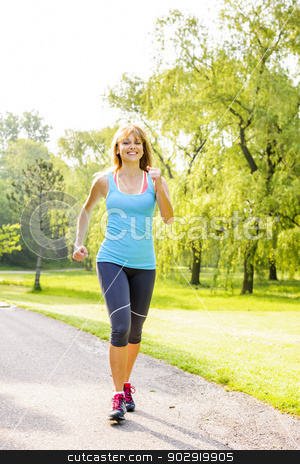 Woman running in park stock photo, Smiling woman exercising on running path in green summer park by Elena Elisseeva
