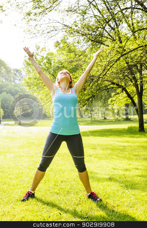 Woman exercising in park stock photo, Female fitness instructor stretching at green park in the morning by Elena Elisseeva