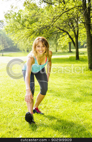 Woman stretching in park stock photo, Female fitness instructor exercising in green park by Elena Elisseeva