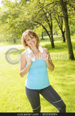 Woman smiling after outdoor exercising stock photo, Smiling female fitness instructor standing with towel around neck after exercising in green park by Elena Elisseeva