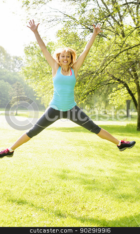 Smiling woman jumping in park stock photo, Happy female fitness instructor jumping exercising outside at green park by Elena Elisseeva