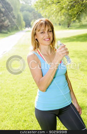 Happy woman drinking water while working out stock photo, Smiling female fitness instructor taking a break with water bottle while exercising outdoor by Elena Elisseeva