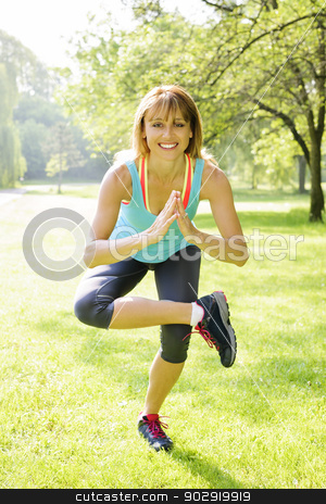 Woman in yoga tree pose stock photo, Smiling female fitness instructor doing yoga tree pose in green park by Elena Elisseeva