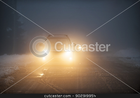 Headlights of car driving in fog stock photo, Bright headlights of a car driving on foggy winter road by Elena Elisseeva