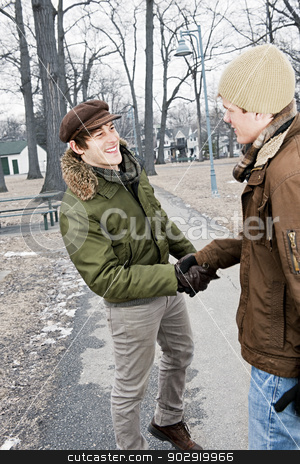 Two men shaking hands in park stock photo, Two young men meeting in winter park shaking hands by Elena Elisseeva