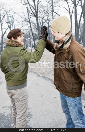 Two men doing high five in park stock photo, Two young men meeting in winter park giving high five by Elena Elisseeva