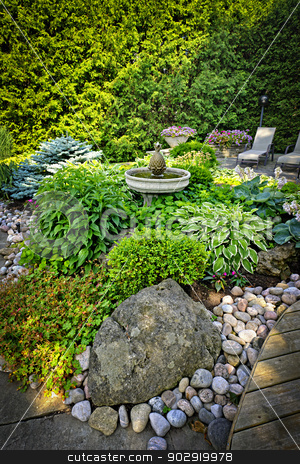 Lush landscaped garden stock photo, Lush perennial garden with fountain plants and trees by Elena Elisseeva
