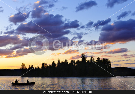 Canoe on lake at sunset stock photo, Silhouette of island and canoe on lake at sunset in Algonquin Park, Canada by Elena Elisseeva