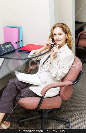 Businesswoman on telephone at office desk stock photo, Thoughtful business woman on phone taking notes in office workstation by Elena Elisseeva