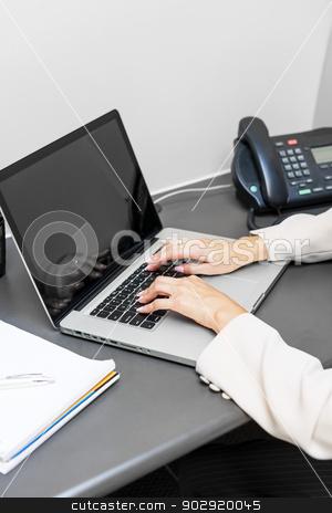 Hands typing on laptop keyboard stock photo, Female hands typing on laptop keyboard at office desk by Elena Elisseeva