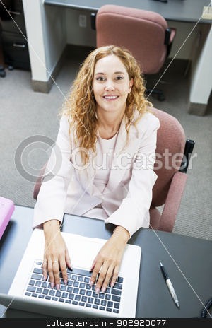 Woman typing on laptop computer at work stock photo, Smiling businesswoman sitting at workstation in office with computer by Elena Elisseeva