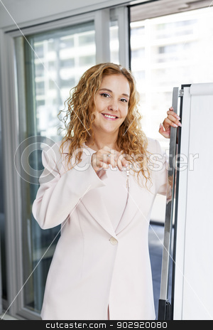 Real estate agent holding keys in office stock photo, Smiling female real estate agent holding house keys in office by Elena Elisseeva
