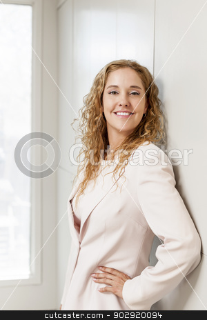 Successful businesswoman standing in hallway stock photo, Smiling happy business woman standing in office hallway by Elena Elisseeva