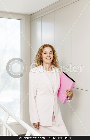 Successful businesswoman standing in hallway stock photo, Happy confident business woman standing in office hallway holding binder by Elena Elisseeva