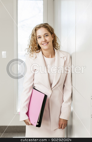 Businesswoman standing in office hallway stock photo, Smiling successful business woman standing in office hallway holding binder by Elena Elisseeva