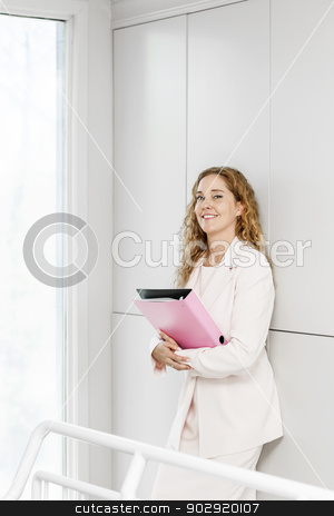 Happy businesswoman standing in hallway stock photo, Confident career business woman standing in office hallway holding binder by Elena Elisseeva