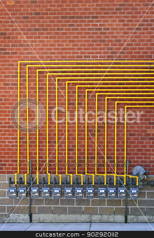 Gas meters on brick wall stock photo, Row of natural gas meters with yellow pipes on building brick wall by Elena Elisseeva