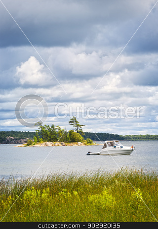 Boat anchored on lake stock photo, Motorboat anchored with dinghy on lake in Georgian Bay, Ontario, Canada by Elena Elisseeva