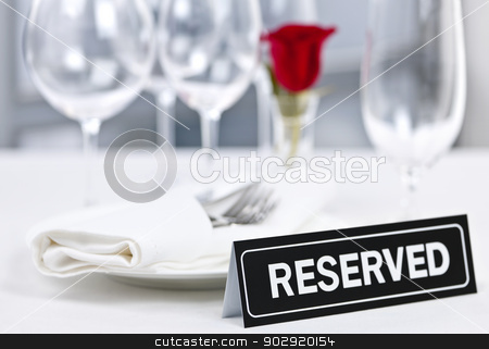 Reserved table at romantic restaurant stock photo, Reserved romantic restaurant table setting with roses plates and cutlery by Elena Elisseeva