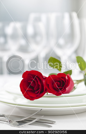 Romantic restaurant dinner setting stock photo, Romantic restaurant table setting for two with roses plates and cutlery by Elena Elisseeva
