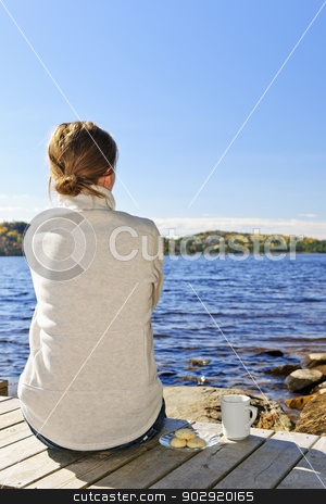 Woman relaxing at lake shore stock photo, Woman sitting on dock relaxing by beautiful lake in Algonquin Park, Canada. by Elena Elisseeva