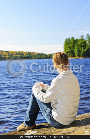 Woman relaxing at lake shore stock photo, Woman sitting on rock relaxing by beautiful lake in Algonquin Park, Canada. by Elena Elisseeva