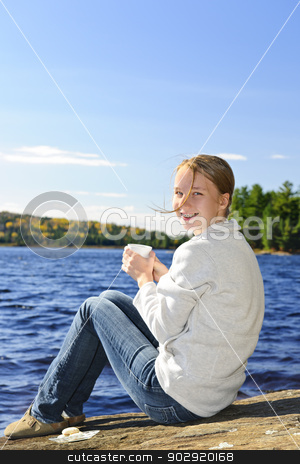 Young woman relaxing at lake shore stock photo, Young woman sitting with beverage on rock relaxing by beautiful lake in Algonquin Park, Canada by Elena Elisseeva