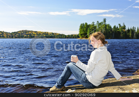 Young woman relaxing at lake shore stock photo, Young woman sitting with beverage on rock relaxing by beautiful lake in Algonquin Park, Canada. by Elena Elisseeva