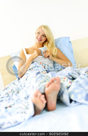 Woman sitting in bed with coffee cup stock photo, Happy blonde woman drinking coffee and relaxing in bed in the morning by Elena Elisseeva