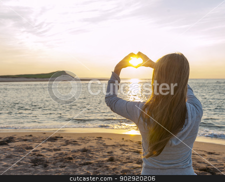 Girl holding hands in heart shape at beach stock photo, Blonde young girl holding hands in heart shape framing setting sun at sunset on ocean beach by Elena Elisseeva