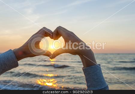 Hands in heart shape framing sun stock photo, Hands and fingers in heart shape framing setting sun at sunset over ocean by Elena Elisseeva