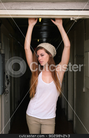 Young Woman Hallway stock photo, Young woman standing in a hallway looking up. by Henrik Lehnerer