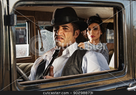 Sneering 1920s Gangster Driver stock photo, Sneering 1920s vintage gangsters inside automobile by Scott Griessel