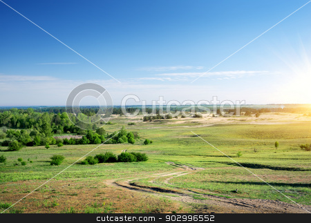 Country road through the plain stock photo, Country road through the plain at sunrise by Givaga